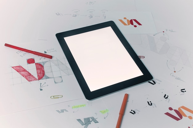 Creative workplace of a graphic designer with tablet. development of a logo for the company. drawings and sketches on paper in a art studio office.