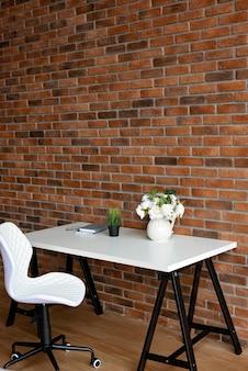 크리 에이 티브 직장 로프트 벽돌 벽과 흰색 테이블에 액세서리. 복사 공간, 소프트 선택적 포커스.