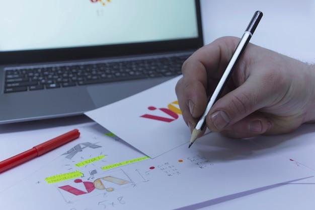 그래픽 디자이너의 창의적인 직장. 사무실에 있는 한 남자가 인쇄된 스케치와 노트북의 배경에 대해 테이블에 로고를 개발하고 있습니다.