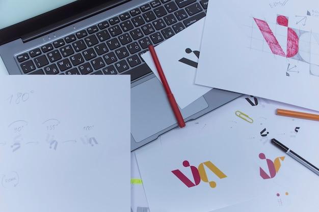 그래픽 디자이너의 창의적인 직장. 회사 로고 개발. 아트 스튜디오 사무실에서 종이에 그림과 스케치.