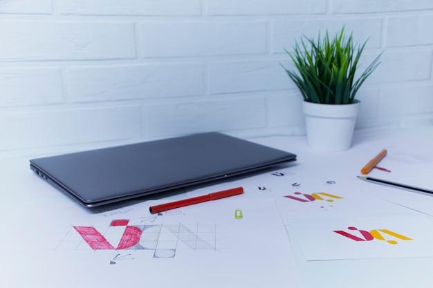노트북이 있는 그래픽 디자이너의 창의적인 작업 공간. 회사 로고 개발. 아트 스튜디오 사무실에서 종이에 그림과 스케치. 프리미엄 사진