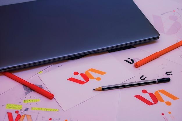 노트북이 있는 그래픽 디자이너의 창의적인 작업 공간. 회사 로고 개발. 아트 스튜디오 사무실에서 종이에 그림과 스케치.