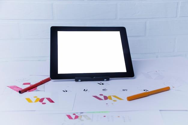 태블릿을 사용하는 그래픽 디자이너의 창의적인 작업 공간. 회사 로고 개발. 아트 스튜디오 사무실에서 종이에 그림과 스케치.
