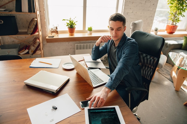 Creative workplace - organized work space as you like for inspiration. man working in office in comfortable attire, relaxed position and messy table. choose atmosphere you want - ideal clear or chaos.