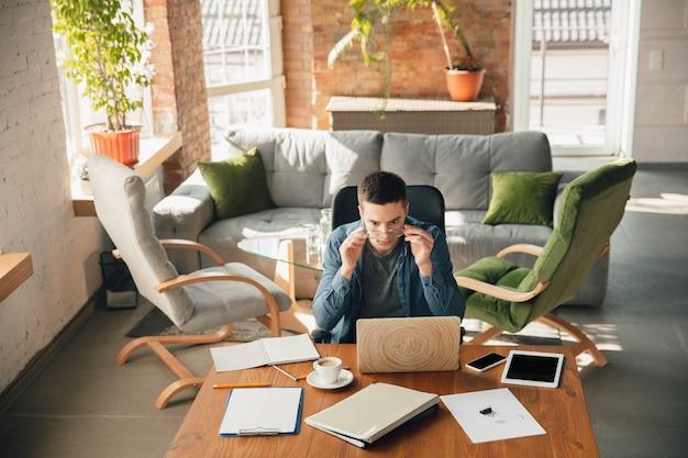 Posto di lavoro creativo: spazio di lavoro organizzato come preferisci per l'ispirazione. uomo che lavora in ufficio in abbigliamento comodo, posizione rilassata e tavolo disordinato. scegli l'atmosfera che desideri - ideale chiaro o caos.