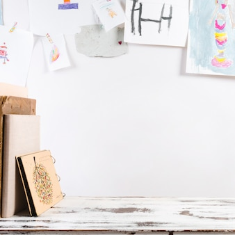 Creative workplace with child's drawings on wall