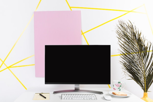 Creative workplace with monitor and palm leaf