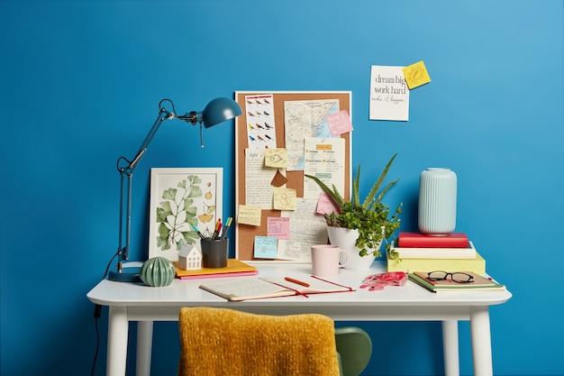 Luogo di lavoro creativo senza persone, blocco note aperto, lampada da scrivania, lavagna con note adesive da ricordare, pianta da interno in vaso, boccale di bevanda.