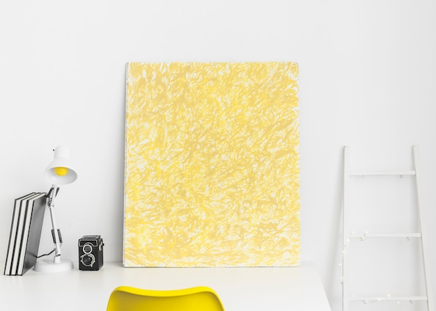 Creative workplace with yellow picture and white ladder