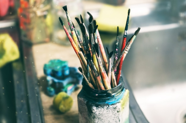 Creative workshop of the artist. paint brushes in a jar. many brushes for painting in one place