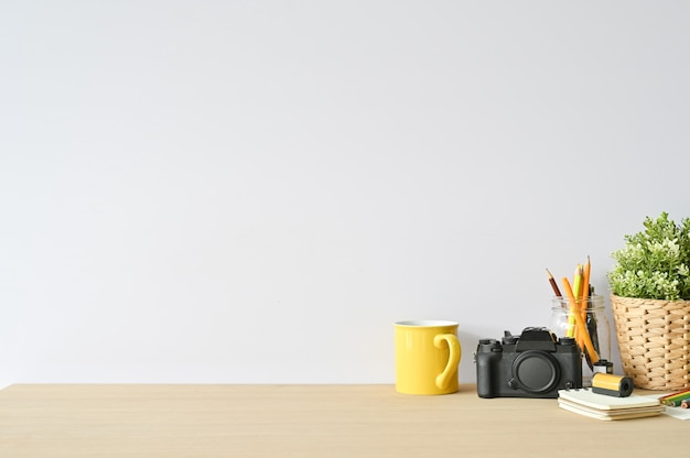Creative workspace camera and office supplies on wood desk with copy space.