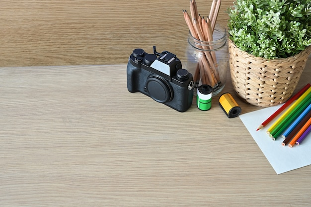 Creative workspace camera and office supplies on wood desk.