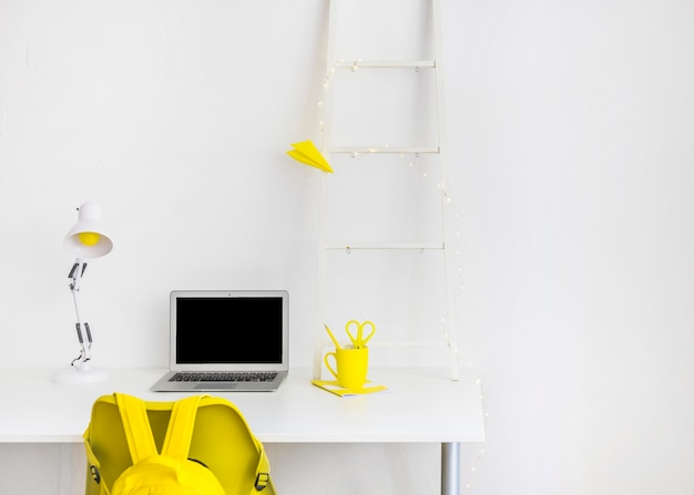 Creative workspace in white and yellow colors with laptop