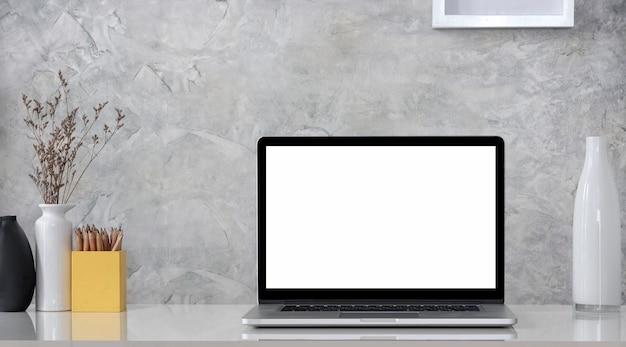 コンクリートの壁を持つ木製のテーブルに空白の画面のラップトップ コンピューターと装飾オブジェクトを備えたクリエイティブなワークスペース