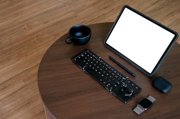 나무 테이블에 빈 화면 태블릿, 키보드 및 가젯이 있는 창의적인 작업 공간.