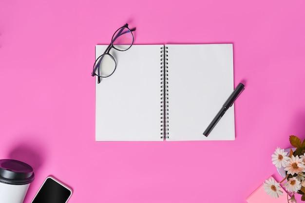 Творческое рабочее место с пустым блокнотом, ручкой, кофейной чашкой и мобильным телефоном на розовом фоне.