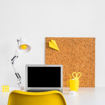 Creative workspace with yellow chair and reading lamp
