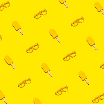 Creative yellow summer pattern of popsicles and sunglasses on bright abstract yellow background
