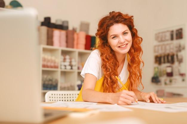 アートスタジオで働く長い赤いウェーブのかかった髪を持つ創造的な若いアーティスト