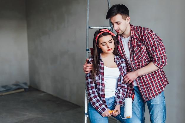 家をリフォームして壁を塗るクリエイティブな若いカップル、彼らは一緒にポーズをとり、最高のものを望んでいます