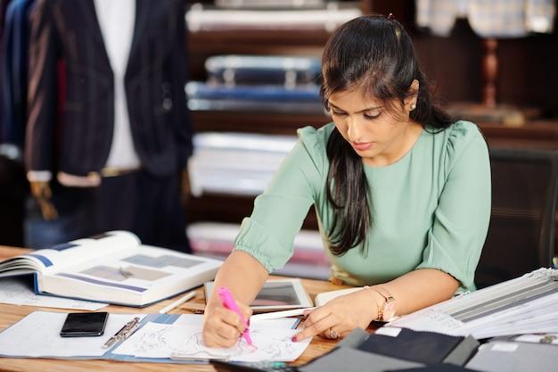 新しいコレクションのスケッチを描く創造的な若いインドのファッションデザイナー