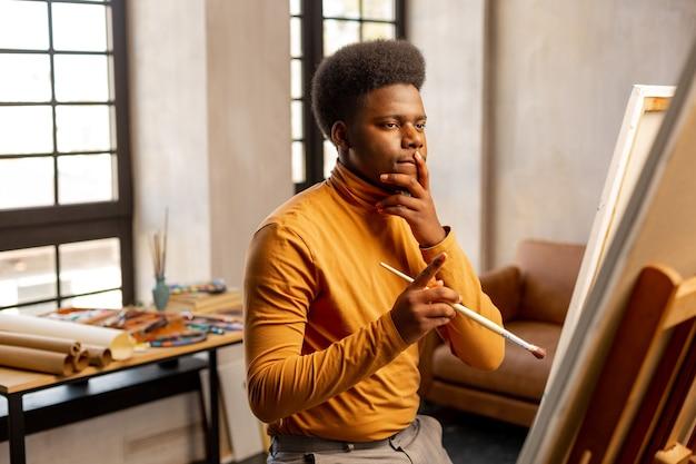 何を描くかを考えながら帆布を見ている創造的な青年
