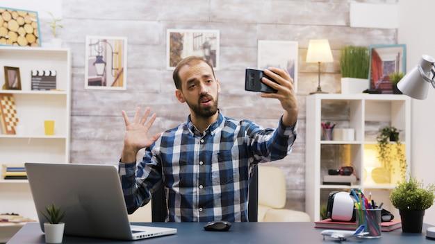 Творческий молодой человек использует свой телефон, чтобы записать новую серию для социальных сетей. известный влиятельный человек. создатель креативного контента.