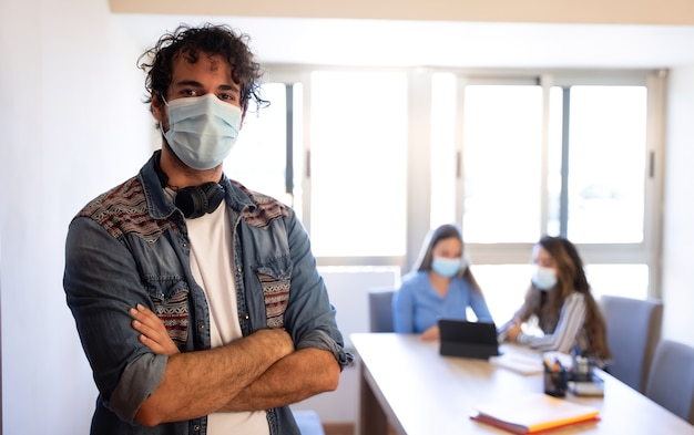 Creative young man with face mask meeting background