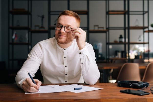 Творческий молодой музыкант в стильных очках пишет музыкальные ноты ручкой