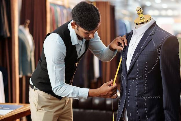 彼が取り組んでいるマネキンのオーダーメイドジャケットを測定する創造的な若いテーラー