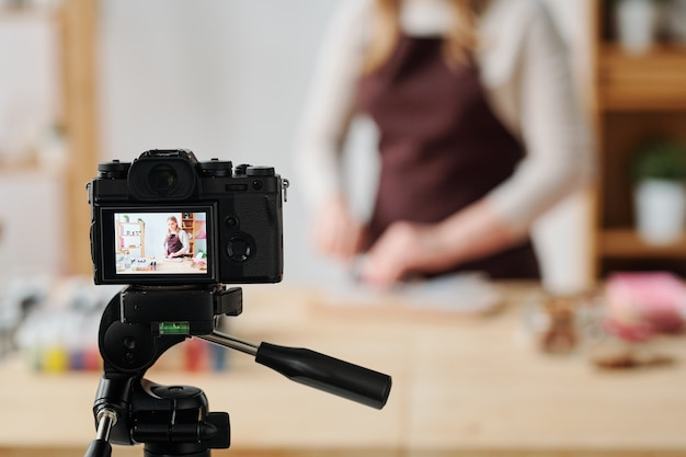 Creative young woman in home camera recording soap making master class for her subscribers