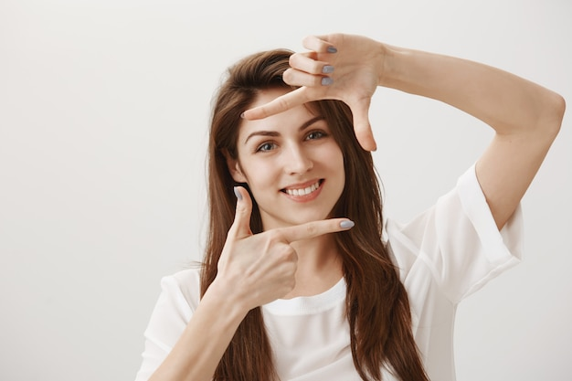 Creative young woman making capture gesture, picturing scene and smiling pleased