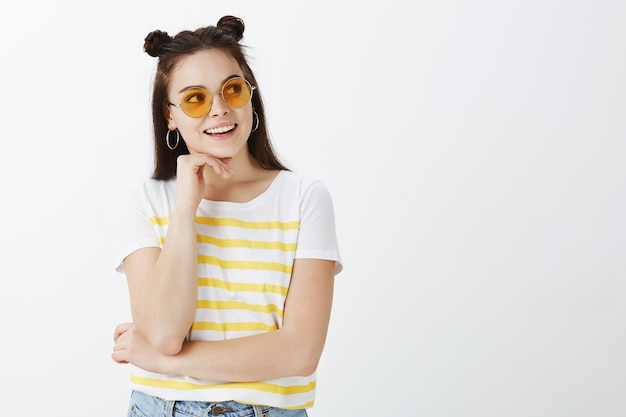 Creative young woman posing with sunglasses against white wall