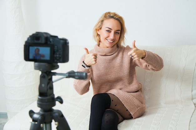 Creative young woman recording video blog for social media network
