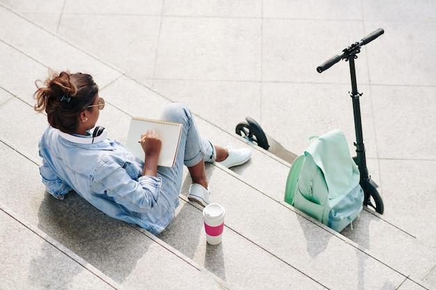 テイクアウトコーヒーとスケッチブックでスケッチを描くと階段に座っている創造的な若い女性