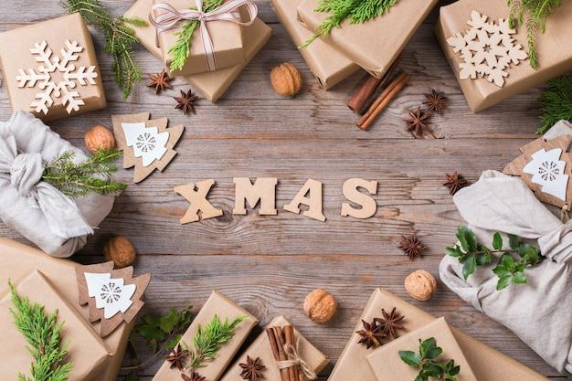 창의적인 제로 웨이스트 크리스마스 컨셉입니다. 수제 친환경 공예 포장지와 일본 전통 스타일의 보자기 패브릭 포장으로 된 선물 상자. 나무 평면도 평면 누워 배경