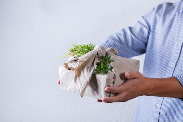 창의적인 제로 웨이스트 크리스마스 컨셉입니다. 친환경 전통 일본식 보자기 천으로 포장된 수제 선물 상자를 주는 손