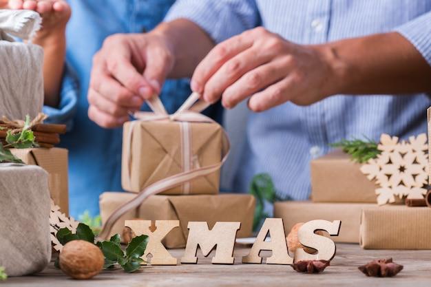 창의적인 제로 웨이스트 크리스마스 컨셉입니다. 행복한 귀여운 소년과 그의 아버지는 손으로 만든 친환경 공예 종이와 전통적인 일본식 후로시키 천으로 선물 상자를 포장합니다. 집에서 가족 시간