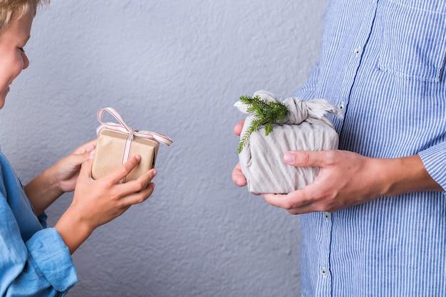 창의적인 제로 웨이스트 크리스마스 컨셉입니다. 친환경 공예 종이와 전통 일본식 보자기로 포장된 수제 선물 상자를 교환하는 사람들. 가족 시간, 축제 준비.