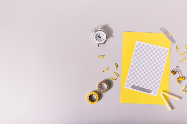 Creatively laid out school supplies of yellow color on desk