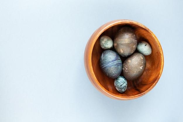 Креативно расписанные пасхальные яйца из курицы и перепелов с натуральным красителем гибискус, выглядят как морские камни в миске на сером столе