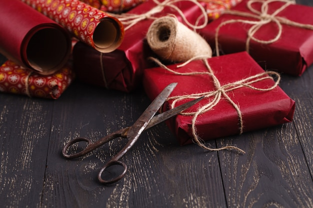 Creatively wrapped and decorated christmas presents in boxes on wooden surface