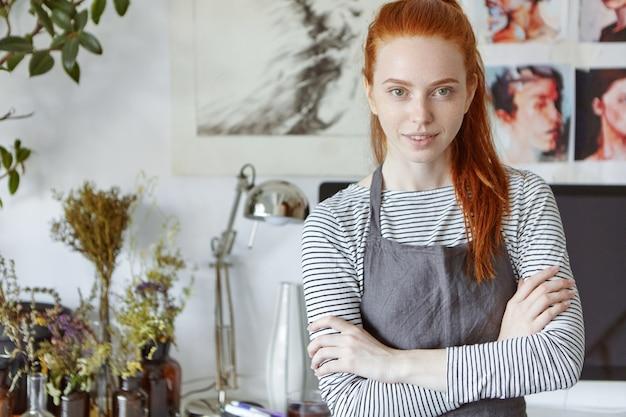 創造性とアートのコンセプト。壁に写真とテーブルの上にボトルに花とワークショップスペースに立っている長い生姜髪の美しい創造的なプロの女性アーティストの上半身ショット