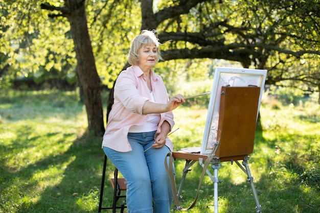 創造性、趣味、芸術、レジャー、人々のコンセプト。夏の緑豊かな公園の野外で屋外のイーゼルに絵を描く、絵筆を持つ幸せな年配の女性アーティストのポートレート。