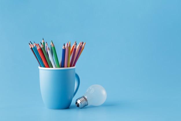 Creativity idea concept with mug oð° pencils and light bulb