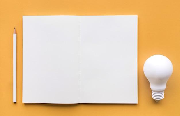 창의력 영감, 파스텔 색상의 전구 및 메모장이있는 아이디어 개념
