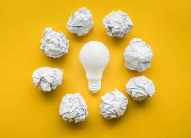 パステルカラーの背景に電球と紙のしわくちゃのボールと創造性のインスピレーション、アイデアの概念。