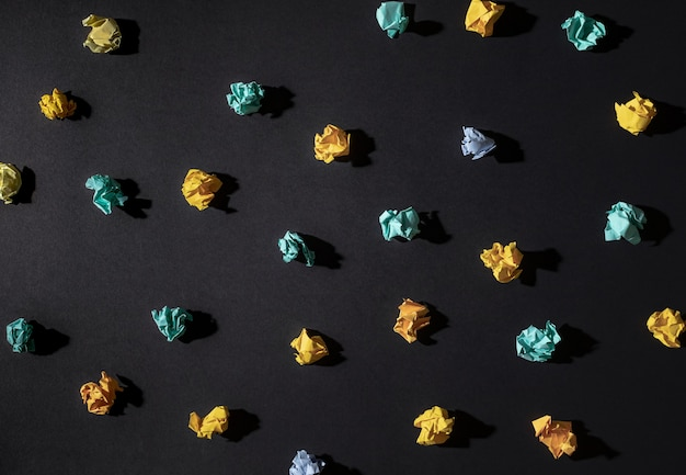 Creativity inspiration,ideas concepts with paper crumpled ball on black color background.flat lay design.
