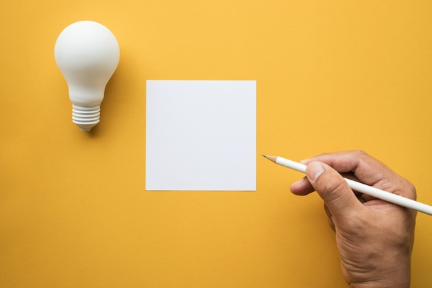 Creativity inspirationideas concepts with lightbulb and notepad on pastel
