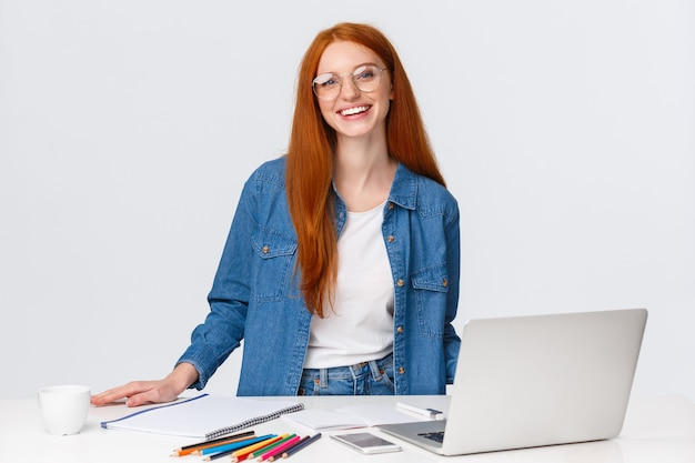 Creativity, lifestyle and education concept. cute charismatic redhead girl in glasses standing near table and laptop, prepare colored pencils and staff to draw, learning art or design online courses